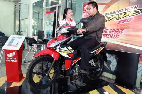 Karyawan Dealer Honda menjelaskan teknologi dan fitur sepeda motor Honda Blade kepada konsumen.  AHM mempersembahkan program Geber Miliaran Honda 2013 bagi para pecinta Honda Revo dan Honda Blade sebagai salah satu upaya perusahaan untuk mengapresiasi konsumen setianya.