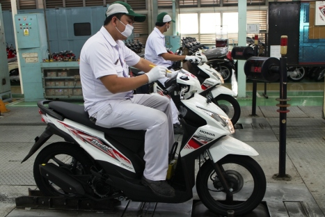 Karyawan AHM melakukan proses final inspeksi sepeda motor Honda BeAT FI di pabrik perakitan AHM, Cibitung. Honda BeAT FI tercatat mampu menguasai 52% pangsa pasar segmen skutik entry level < 125cc di kuartal I/2014.